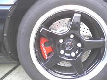 close up: 3 color paint job red caliper, silver letters, cast iron on abutment/caliper bracket.