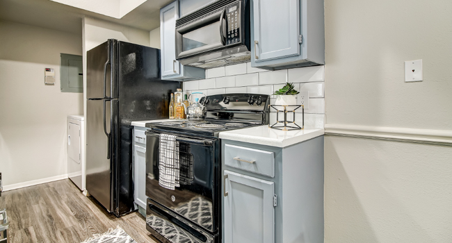 Kitchen with subway tile back-splash, faux-wood floors, and black appliance package