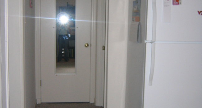 Hallway, kitchen is immediately to the right, bedroom to the left, bathroom far right, closet straight ahead